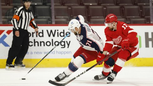 Mar 27, 2021; Detroit, Michigan, USA; Columbus Blue Jackets left wing Nick Foligno (71) skates with the puck defended by Detroit Red Wings defenseman Filip Hronek (17) in the third period at Little Caesars Arena.
