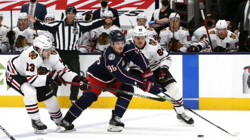 Columbus Blue Jackets center Jack Roslovic (96) splits the defense of Chicago Blackhawks center Mattias Janmark (13) and center David Kampf (64) during the third period at Nationwide Arena.