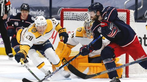 May 5, 2021; Columbus, Ohio, USA; Columbus Blue Jackets right wing Oliver Bjorkstrand (28) passes the puck as Nashville Predators right wing Eeli Tolvanen (28) reaches for the steal during the first period at Nationwide Arena.