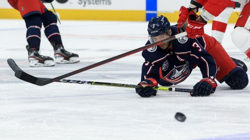 Columbus Blue Jackets defenseman Seth Jones (3) passes the puck as he falls to the ice against Detroit Red Wings center Luke Glendening (41) in the third period at Nationwide Arena.