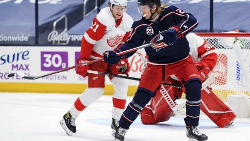 May 8, 2021; Columbus, Ohio, USA; Columbus Blue Jackets right wing Patrik Laine (29) deflects the puck in the air along side Detroit Red Wings defenseman Dennis Cholowski (21) in the third period at Nationwide Arena.