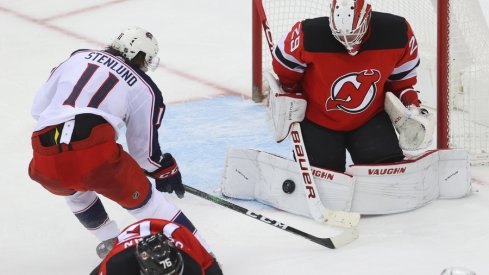 New Jersey Devils goaltender Mackenzie Blackwood (29) makes a save on Columbus Blue Jackets center Kevin Stenlund (11) during overtime at Prudential Center.
