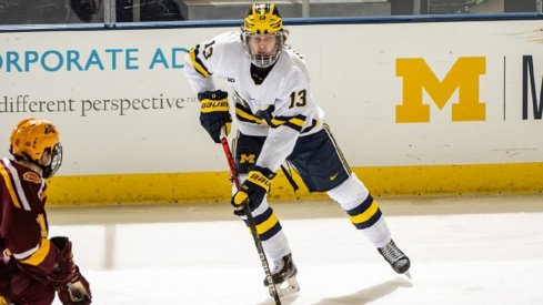 Kent Johnson skates with the puck against the University of Minnesota