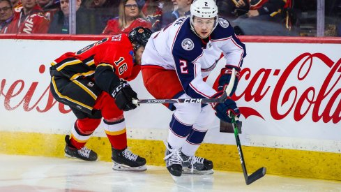 Mar 4, 2020; Calgary, Alberta, CAN; Columbus Blue Jackets defenseman Andrew Peeke (2) and Calgary Flames center Tobias Rieder (16) battle for the puck during the third period at Scotiabank Saddledome.