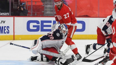 Jan 18, 2021; Detroit, Michigan, USA; Columbus Blue Jackets goaltender Joonas Korpisalo (70) makes a save in front of Detroit Red Wings center Michael Rasmussen (27) during the second period at Little Caesars Arena.