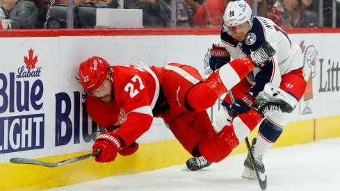 Oct 19, 2021; Detroit, Michigan, USA; Detroit Red Wings center Michael Rasmussen (27) and Columbus Blue Jackets center Gustav Nyquist (14) battle for the puck in the second period at Little Caesars Arena.