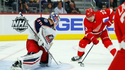Oct 19, 2021; Detroit, Michigan, USA; Detroit Red Wings right wing Lucas Raymond (23) tries to score on Columbus Blue Jackets goaltender Joonas Korpisalo (70) in the second period at Little Caesars Arena.