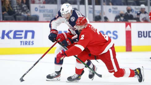 Oct 19, 2021; Detroit, Michigan, USA; Columbus Blue Jackets left wing Eric Robinson (50) and Detroit Red Wings defenseman Nick Leddy (2) battle for the puck in the first period at Little Caesars Arena.