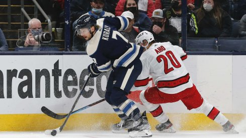 Oct 23, 2021; Columbus, Ohio, USA; Columbus Blue Jackets center Sean Kuraly (7) and Carolina Hurricanes left wing Sebastian Aho (20) battle for the puck during the first period at Nationwide Arena.