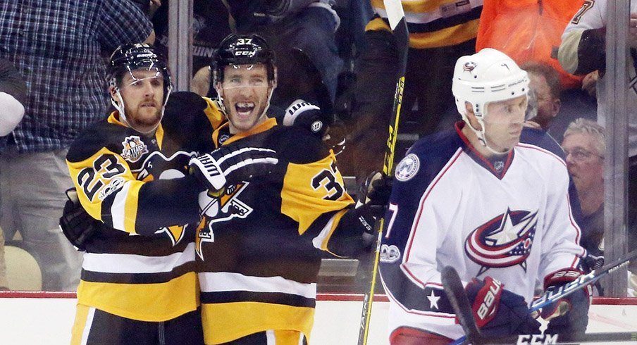 Pittsburgh Penguins left wing Scott Wilson (23) and right wing Carter Rowney (37) celebrate a goal by Rowney as Columbus Blue Jackets defenseman Jack Johnson (7) skates away.