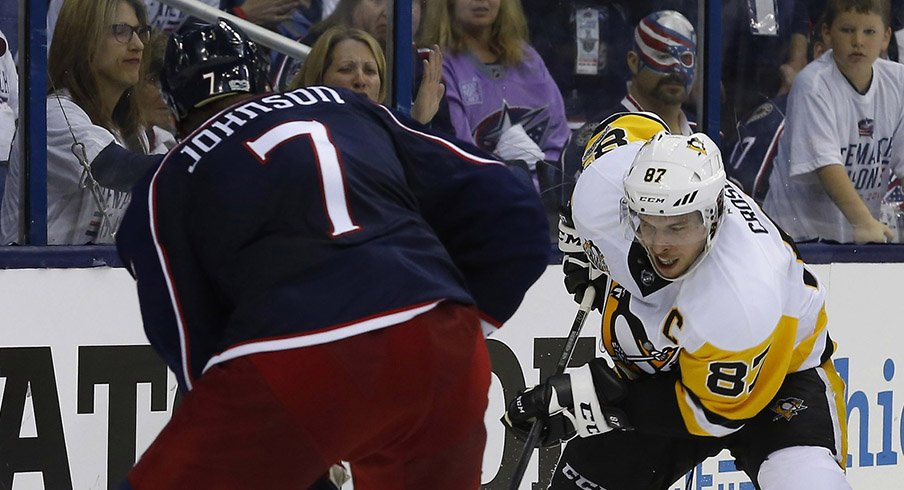 Jack Johnson of the Columbus Blue Jackets meets the Pittsburgh Penguins' Sidney Crosby behind the net.