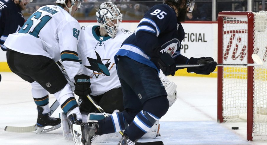 Jets forward Mathieu Perrault slips a puck past Sharks goaltender Martin Jones