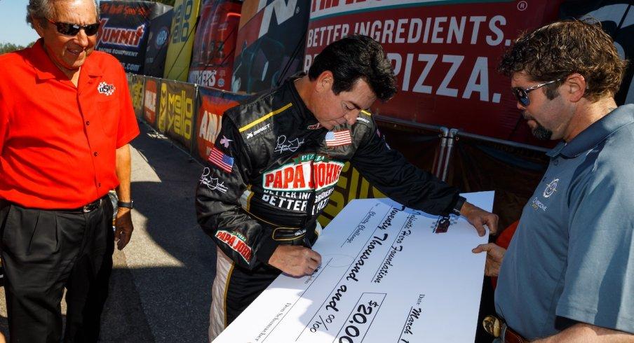 Papa John signs a big check at a racing event