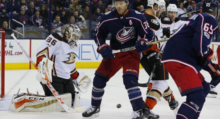 Anaheim Ducks goaltender John Gibson attempts to stop a puck against the Columbus Blue Jackets