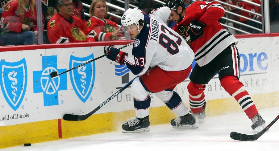 Blue Jackets prospect Calvin Thurkauf battles for a loose puck during preseason action against the Chicago Blackhawks.