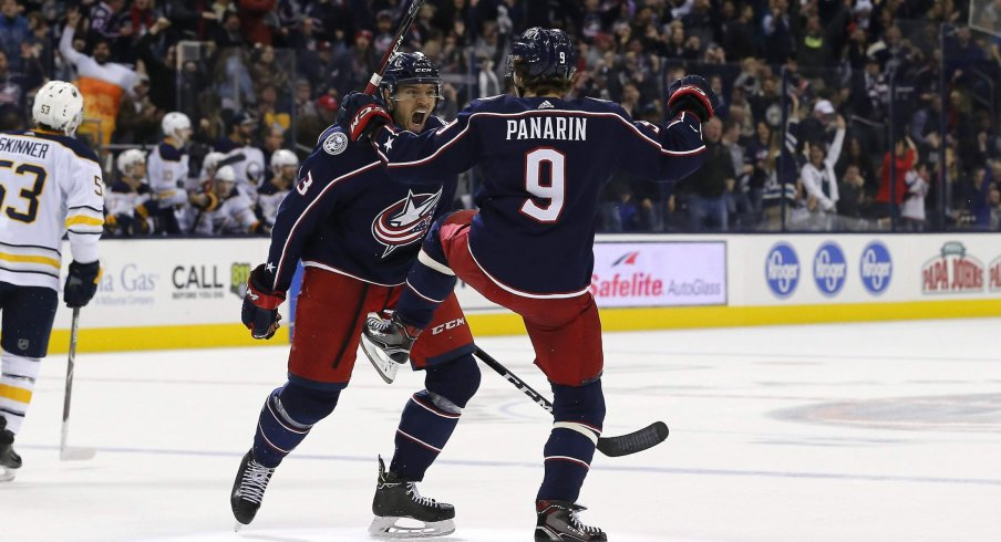 Artemi Panarin celebrates with Seth Jones after his overtime-winning goal against the Sabres on Saturday night.