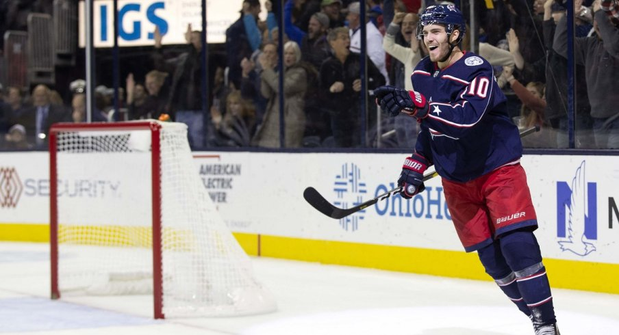 Alexander Wennberg celebrates his first goal of the season by pointing at Seth Jones, who set him up.