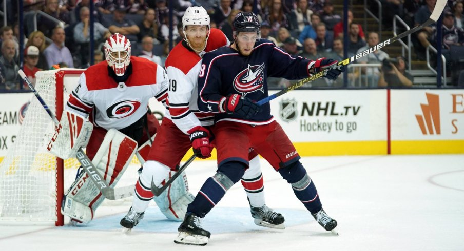 Pierre-Luc Dubois battles with Dougie Hamilton in front of Curtis McElhinney