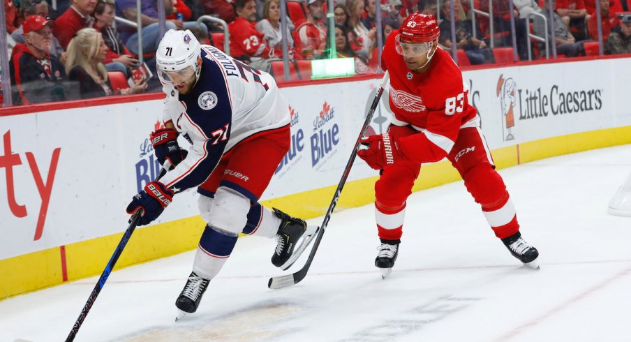 Columbus Blue Jackets captain Nick Foligno protects the puck away from Detroit Red Wings defenseman Trevor Daley during a game at Little Caesars Arena.