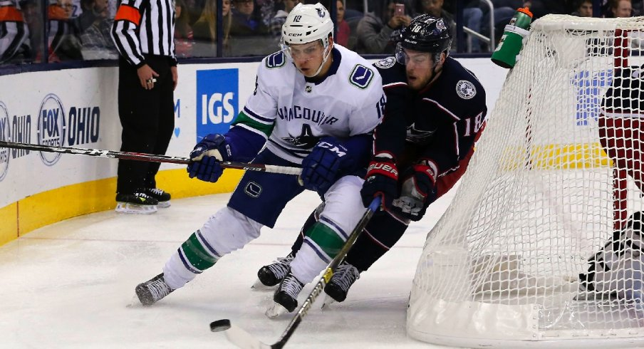 Jake Virtanen carries the puck against Pierre-Luc Dubois in the Vancouver Canucks beat the Columbus Blue Jackets 3-2