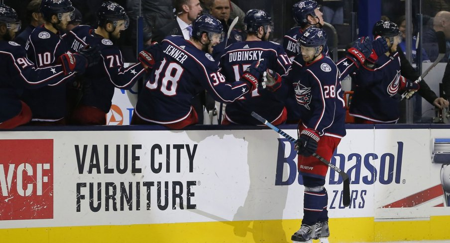 Oliver Bjorkstrand celebrates a goal with the Blue Jackets bench