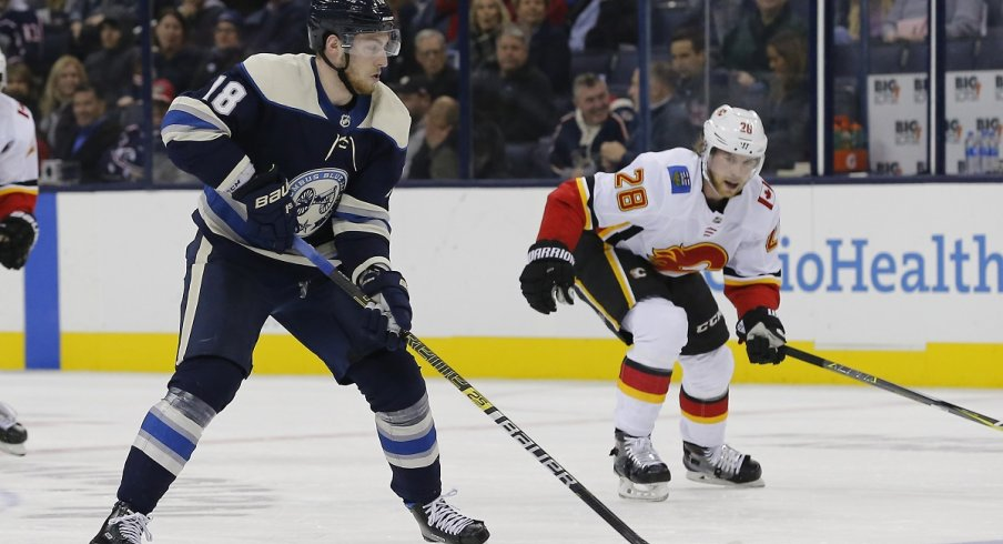 Pierre-Luc Dubois looks to move the puck in The Blue Jackets 9-6 loss to the Calgary Flames