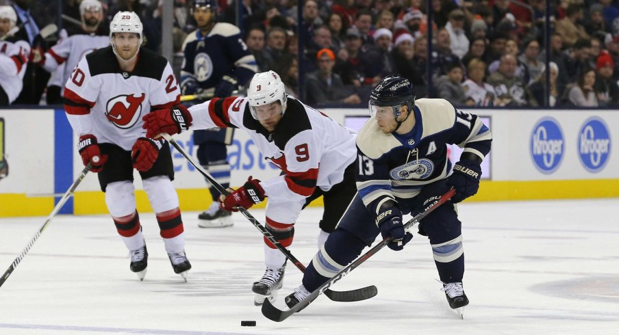 Cam Atkinson skates against Taylor Hall as the Columbus Blue Jackets take on the New Jersey Devils