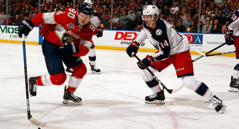 Dean Kukan fights for the puck for the Columbus Blue Jackets in a 4-3 overtime victory against the Florida Panthers.