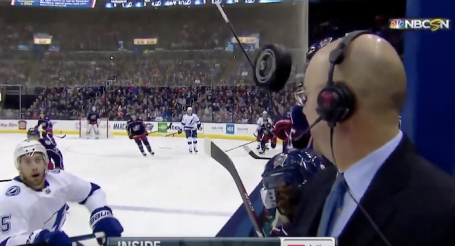 Pierre McGuire narrowly escapes disaster during Monday's game between the Blue Jackets and Lightning at Nationwide Arena.