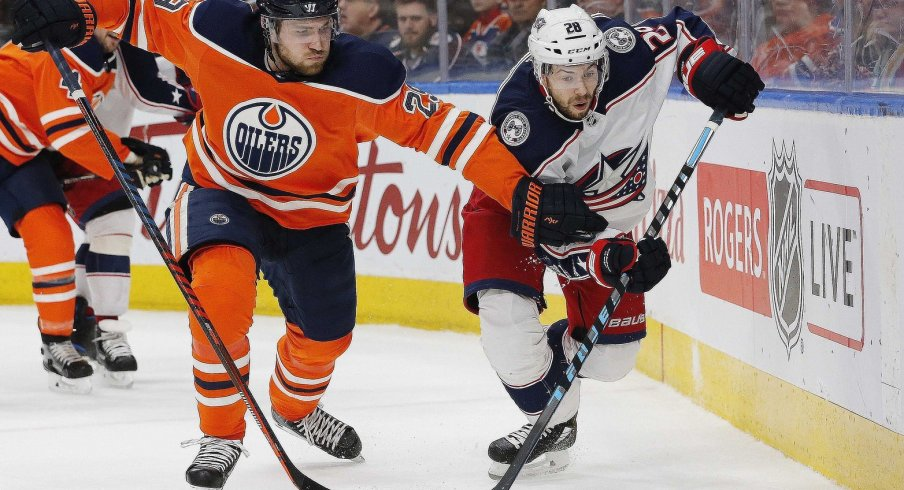 Edmonton Oilers forward Leon Draisaitl (29) and Columbus Blue Jackets forward Oliver Bjorkstrand (28) battle for a loose puck during the second period at Rogers Place.