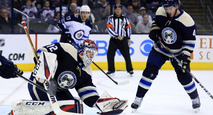 Sergei Bobrovsky attempts to make the save as Scott Harrington reacts against the Winnipeg Jets in the first period at Nationwide Arena.