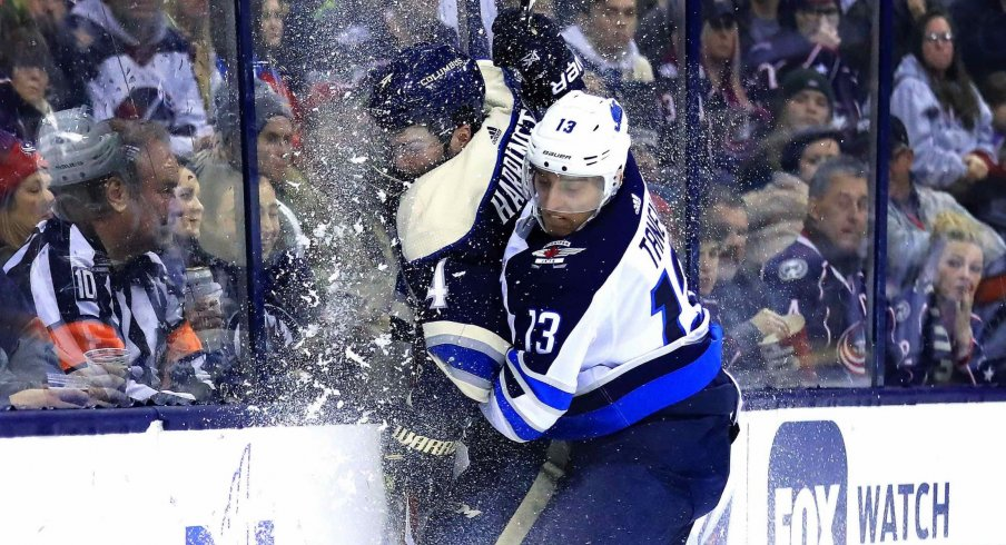 Columbus Blue Jackets defenseman Scott Harrington (4) is checked into the glass by Winnipeg Jets left wing Brandon Tanev (13) in the third period at Nationwide Arena.