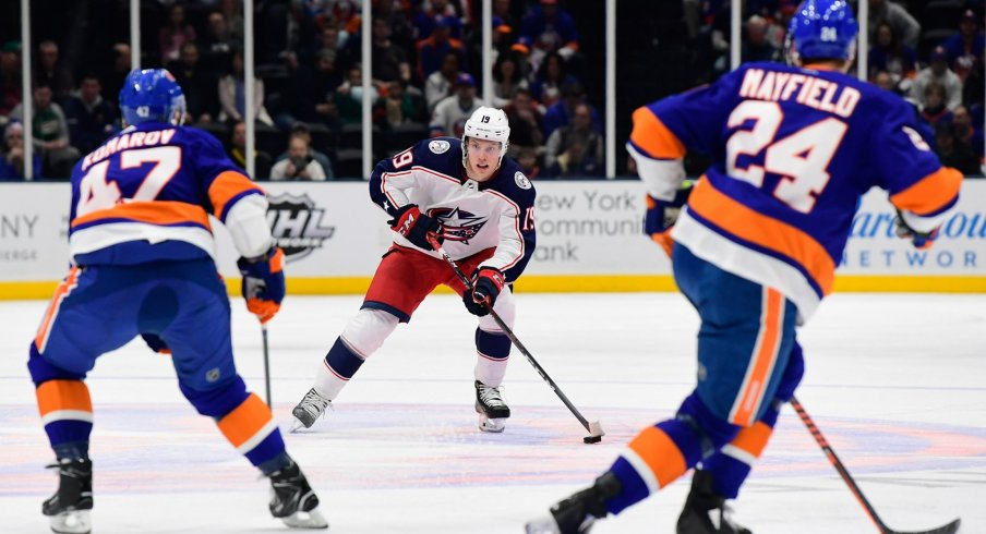 Columbus Blue Jackets center Ryan Dzingel (19) skates with the puck while being defended by New York Islanders right wing Leo Komarov (47) and defenseman Scott Mayfield (24) during the first period at Nassau Veterans Memorial Coliseum.
