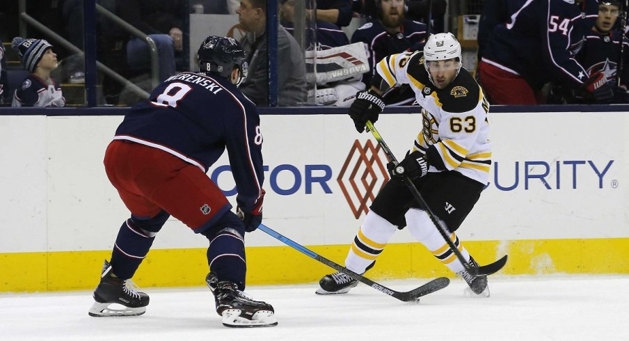 Zach Werenski takes the puck away from Brad Marchand in a victory over the Boston Bruins on Tuesday night.