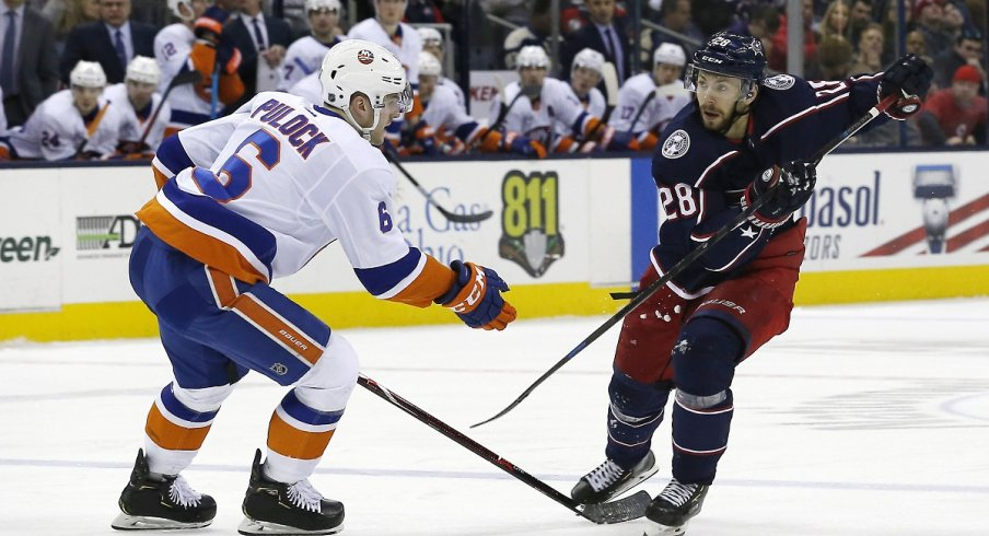 Oliver Bjorkstrand chips the puck past defenseman Ryan Pulock of the New York Islanders