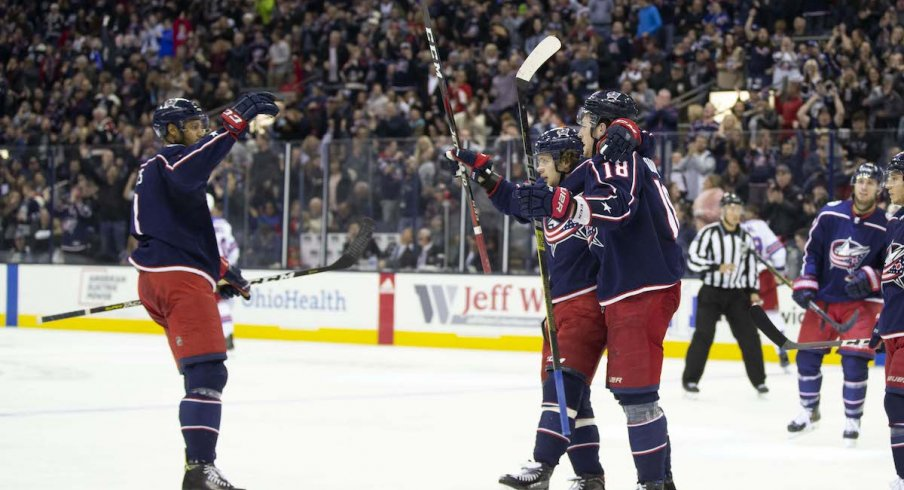 Seth Jones, Artemi Panarin and Pierre-Luc Dubois celebrate a goal scored against the New York Rangers at Nationwide Arena.
