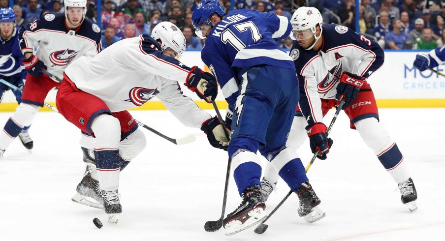 Zach Werenski and Seth Jones tie up Alex Killorn in Game 1 against the Tampa Bay Lightning