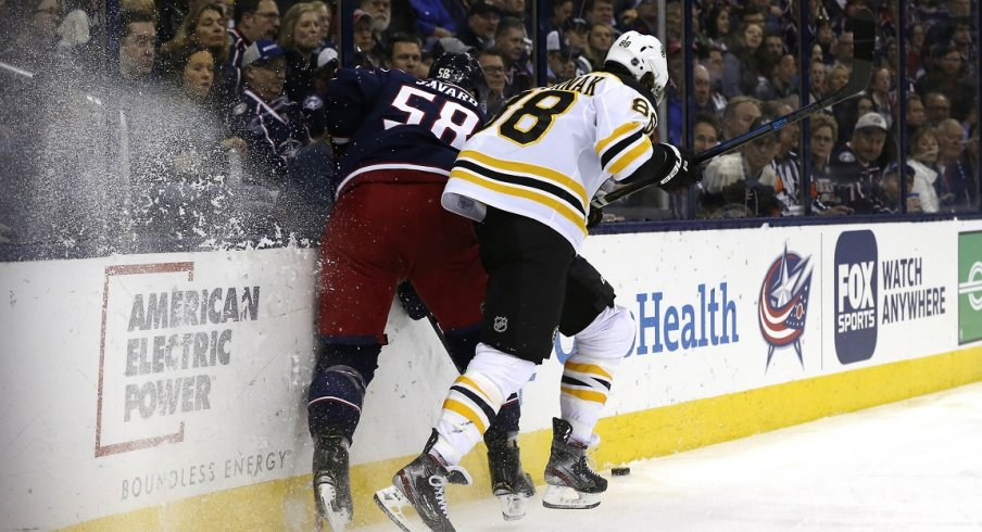 Boston Bruins right wing David Pastrnak (88) checks Columbus Blue Jackets defenseman David Savard (58) during the first period at Nationwide Arena.