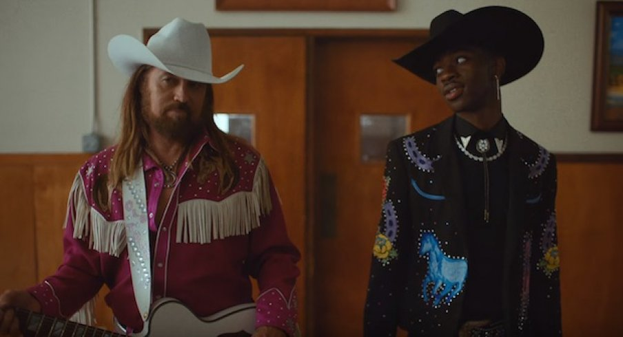 "Lil Nas X and Billy Ray Cyrus walk into a town hall during their music video for ""Old Town Road"""