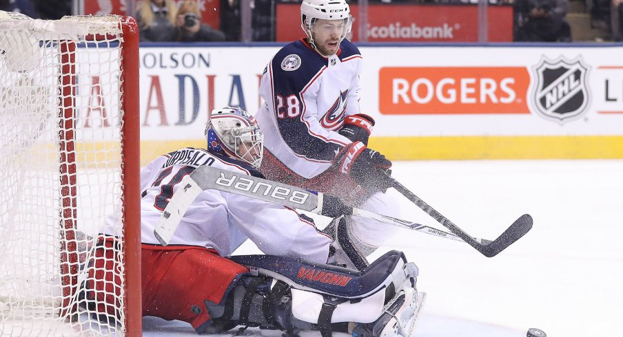 Feb 14, 2018; Toronto, Ontario, CAN; Columbus Blue Jackets goalie Joonas Korpisalo (70) makes a save as right wing Oliver Bjorkstrand (28) goes after the loose puck against the Toronto Maple Leafs at Air Canada Centre. The Maple Leafs beat the Blue Jackets 6-3