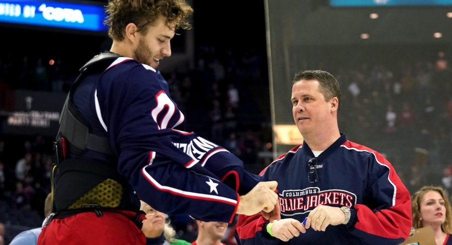 Hockey fan Doug Vance receives the jersey off the back of Columbus Blue Jackets center Alexander Wennberg (10) after a game against the Carolina Hurricanes at Nationwide Arena.