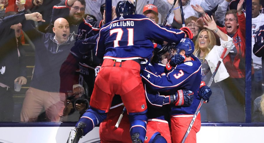 Columbus Blue Jackets forward Nick Foligno jumps onto his teammates to celebrate a goal scored against the Tampa Bay Lightning during the 2019 Stanley Cup Playoffs at Nationwide Arena.