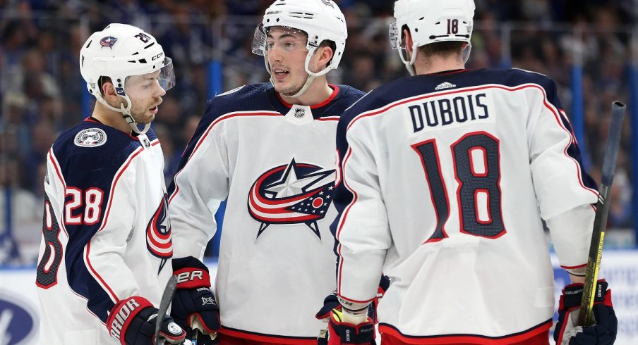 Zach Werenski, Oliver Bjorkstrand, and Pierre-Luc Dubois chat during the second period of game one of the first round of the 2019 Stanley Cup Playoffs against the Tampa Bay Lightning