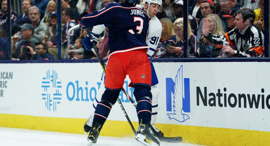 Columbus Blue Jackets defenseman skates toward John Tavares of the Toronto Maple Leafs during his team's home opener at Nationwide Arena.