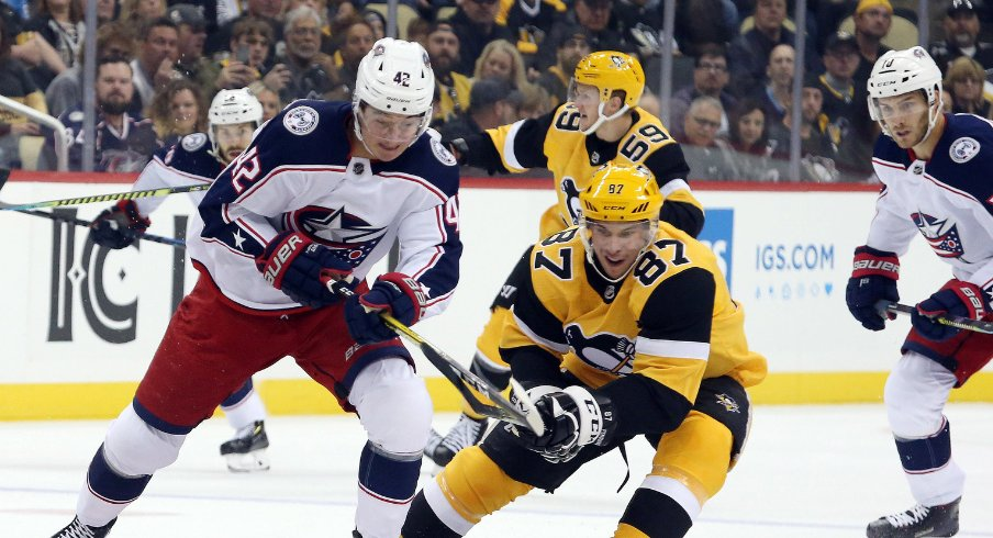 Columbus Blue Jackets forward Alexandre Texier battles with Pittsburgh Penguins forward Sydney Crosby during the Penguins' home opener for the 2019 NHL Regular Season.
