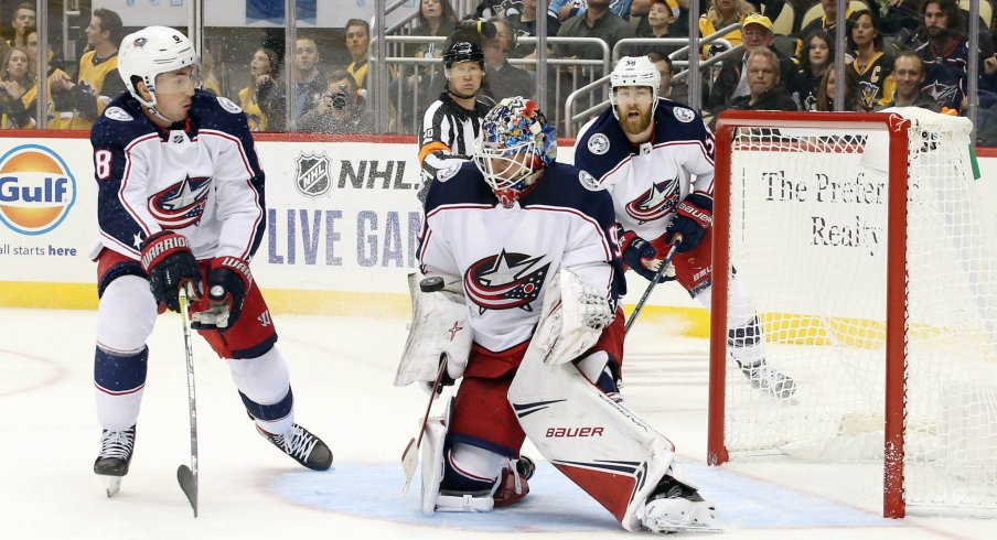Oct 5, 2019; Pittsburgh, PA, USA; Columbus Blue Jackets goaltender Elvis Merzlikins (90) makes a save as defenseman Zach Werenski (8) defends against the Pittsburgh Penguins during the second period at PPG PAINTS Arena. The Penguins won 7-2.