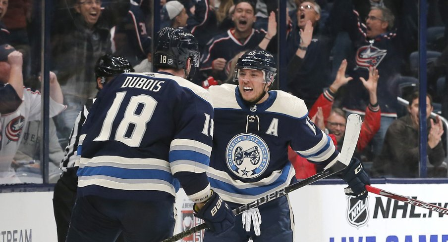 Columbus Blue Jackets forwards Pierre-Luc Dubois and Cam Atkinson celebrate after a game-winning goal in overtime to defeat the Carolina Hurricanes at Nationwide Arena during October of 2019.