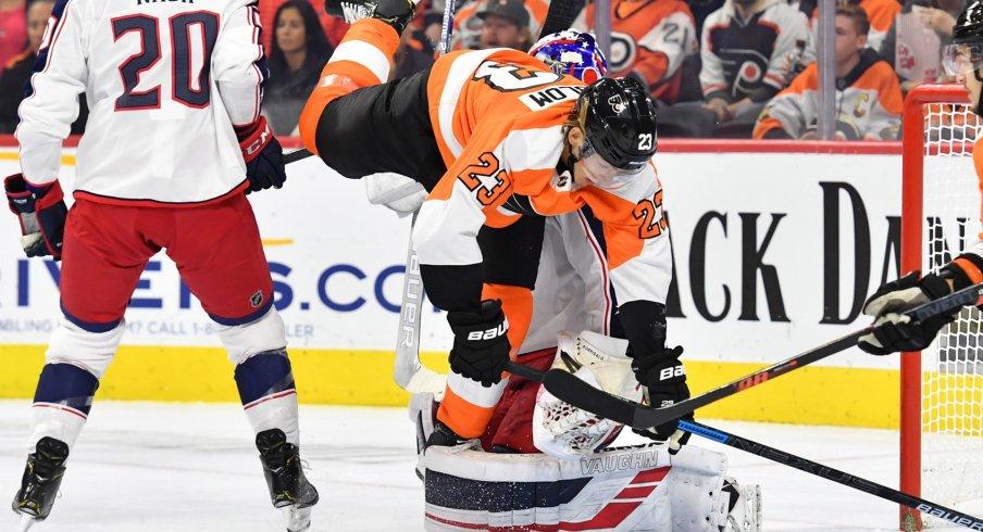 Oct 26, 2019; Philadelphia, PA, USA; Philadelphia Flyers left wing Oskar Lindblom (23) trips over Columbus Blue Jackets goaltender Joonas Korpisalo (70) during the second period at Wells Fargo Center.