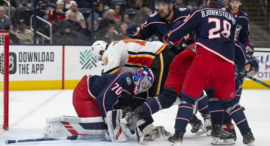 Nov 2, 2019; Columbus, OH, USA; Columbus Blue Jackets goaltender Joonas Korpisalo (70) covers the puck while Calgary Flames left wing Matthew Tkachuk (19) falls on him during the game at Nationwide Arena. Mandatory Credit: Jason Mowry-USA TODAY Sports