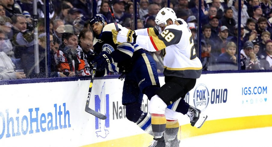 Columbus Blue Jackets defenseman Seth Jones (3) is checked along the boards by Vegas Golden Knights left wing William Carrier (28) in the third period at Nationwide Arena.